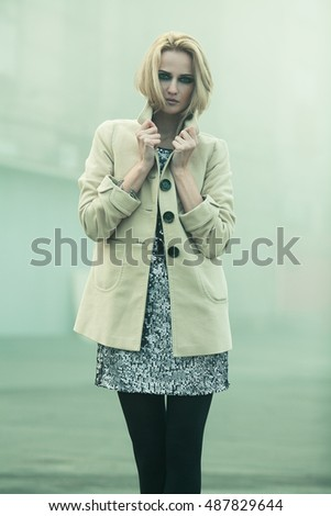 After party concept. Emotive portrait of beautiful blonde with trendy haircut in beige coat. Perfect make-up. Smoky eyes. Haute couture style. Foggy weather. Outdoor shot