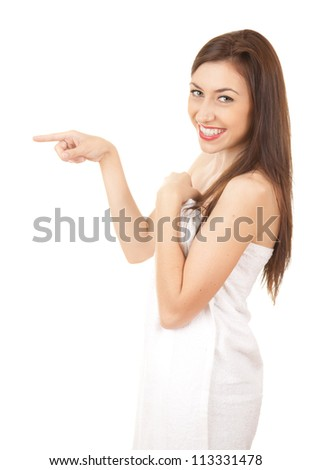 after shower, happy teen girl in towel pointing ahead, white background - stock photo
