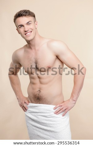 After shower. Young smiling attractive topless man standing with towel on his hips against isolated background - stock photo