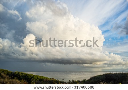 After storm. Spectacular towering white cumulonimbus cloud formation formed in the sky above hills and mountains in a weather and nature background - stock photo