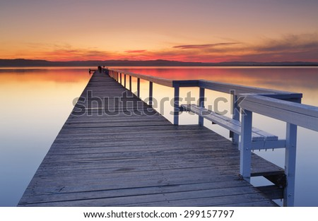 After sunset at Long Jetty, fiery red clouds and reflections in Tuggerah Lake, Central Coast NSW, Australia