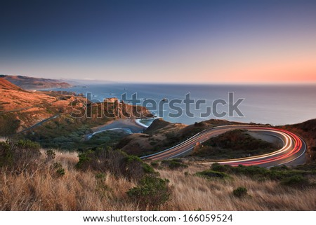 After sunset on the Pacific Ocean looking down the famous highway 1 as evening traffic travels in both directions.  - stock photo