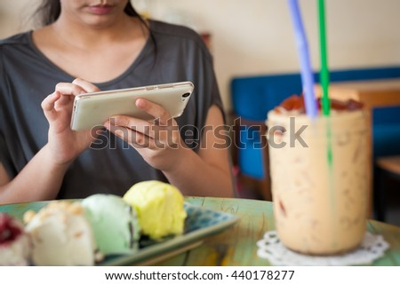 Afternoon scene of young woman using smartphone for social networking in ice cream cafe on weekend. Modern lifestyle with technology concept.