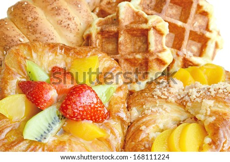 Afternoon snack serving with bread, waffle and Danish pastry topping with strawberry, kiwi and peach. - stock photo