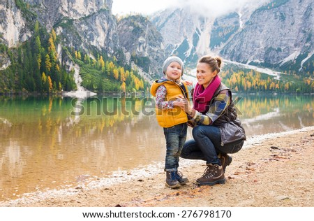 Against a background of autumn colours and leaves, a mother in hiking gear is kneeling and smiling next to her daughter. The mountains and trees are reflected in the lake. - stock photo