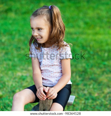 against background of green glade small, pretty girl (child) is riding on swing, looking away
