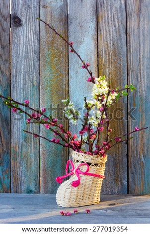 against old colored wooden boards in a boot, wattled from rods, a bouquet from the blossoming branches of plum and a peach, some flowers of a peach fell - stock photo