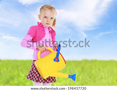 against the blue sky and green grass girl with garden watering. - stock photo