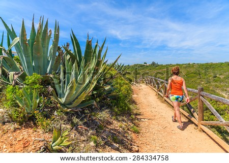 Agave plant and young woman tourist walking on cliff path in Algarve region, Portugal