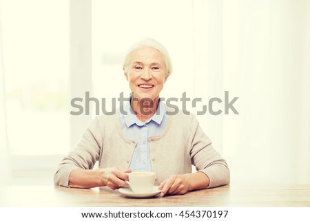 age, drink and people concept - happy smiling senior woman with cup of coffee at home