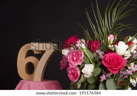 Age in figures next to a bouquet of flowers on a black background - stock photo