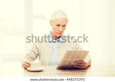 age, leisure and people concept - senior woman drinking coffee and reading newspaper at home