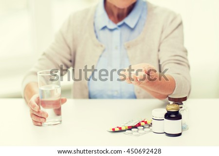 age, medicine, health care and people concept - close up of senior woman with pills and glass of water at home - stock photo