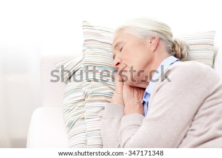 age, relax and people concept - happy senior woman sleeping on pillow at home - stock photo