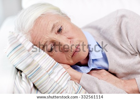 age, sadness, trouble, problem and people concept - sad senior woman sleeping on pillow at home - stock photo