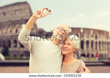 age, tourism, travel, technology and people concept - senior couple with camera taking selfie on street over coliseum background - stock photo