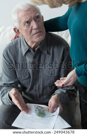 Aged afraid man looking at his bottom line - stock photo