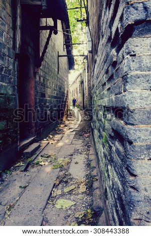 aged alley with stone wall - stock photo