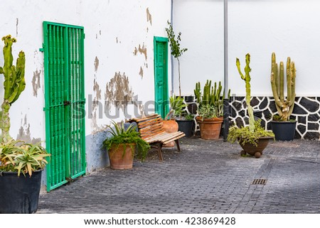 Aged and ancient entrance doors with bench and potted plants.  Exterior of old building with green painted front door in shabby vintage style, image for travel and architectural blog - stock photo