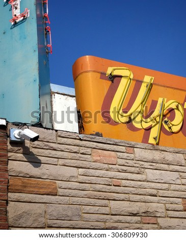 aged and worn neon sign on building                                - stock photo