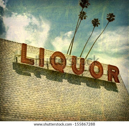 aged and worn vintage liquor store sign with palm trees                                - stock photo
