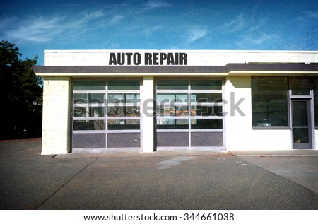 aged and worn vintage photo of abandoned auto repair garage                 - stock photo