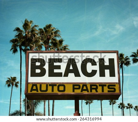aged and worn vintage photo of auto parts sign with palm trees - stock photo