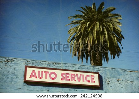 aged and worn vintage photo of auto service sign with palm trees - stock photo