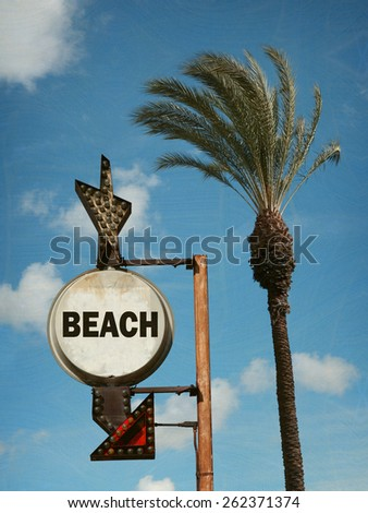aged and worn vintage photo of beach sign with palm tree                                - stock photo