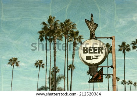 Aged and worn vintage photo of  beer sign on beach with palm trees                             - stock photo