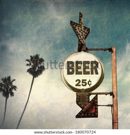 aged and worn vintage photo of beer sign with palm trees - stock photo