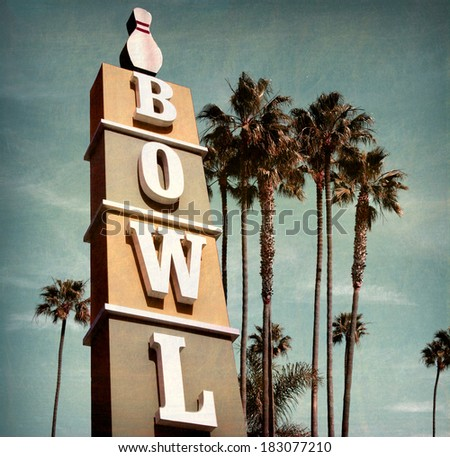 aged and worn vintage photo of bowling alley sign with palm trees - stock photo