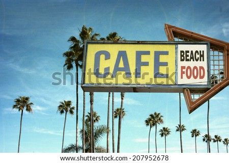 aged and worn vintage photo of cafe sign on beach with palm trees - stock photo