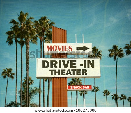 aged and worn vintage photo of drive in theater sign with pal trees                              - stock photo