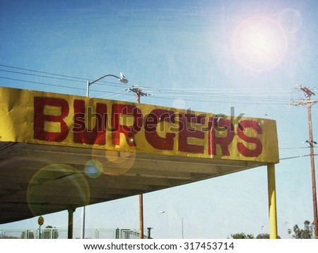 aged and worn vintage photo of fast food burger restaurant sign with sun flare - stock photo