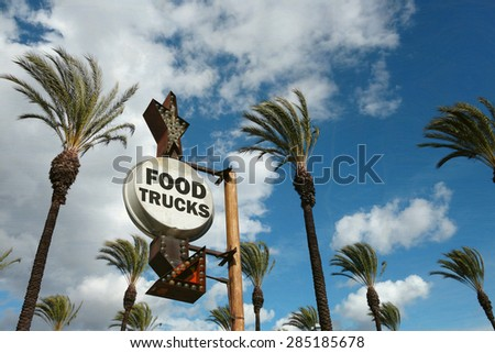 aged and worn vintage photo of food trucks sign with palm trees                             - stock photo