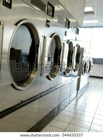 aged and worn vintage photo of laundromat washers and dryers
