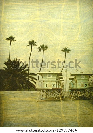aged and worn vintage photo of lifeguard towers on beach with palm trees - stock photo
