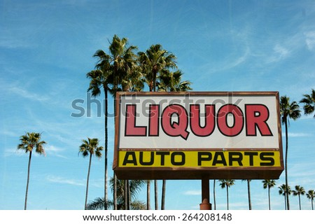 aged and worn vintage photo of liquor and auto parts sign with palm trees - stock photo