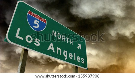 aged and worn vintage photo of los angeles freeway sign with storm in background - stock photo