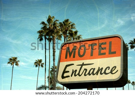 aged and worn vintage photo of motel entrance sign with palm trees - stock photo