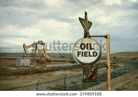 aged and worn vintage photo of oil field sign with derrick in background - stock photo