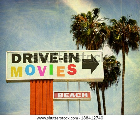 aged and worn vintage photo of retro drive in movies sign with palm trees - stock photo