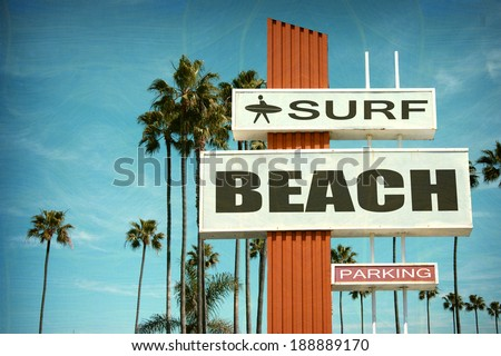 aged and worn vintage photo of surf beach sign with palm trees - stock photo
