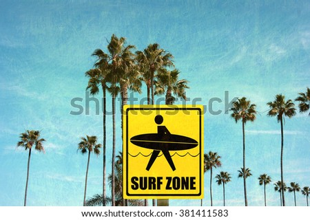 aged and worn vintage photo of surf zone sign on beach with palm trees