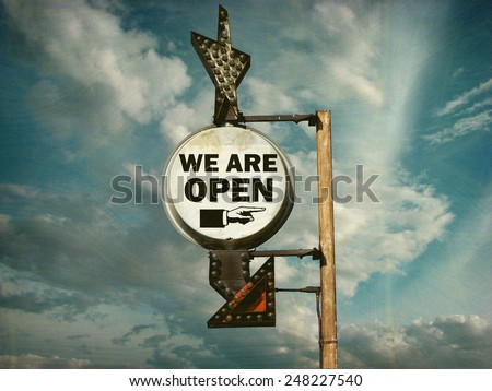 aged and worn vintage photo of we are open sign                            - stock photo