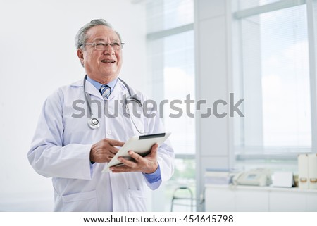 Aged Asian doctor using digital tablet in clinic