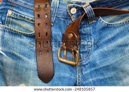 aged blue jeans with unfastened old leather belt