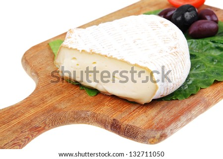 aged brie cheese on wooden platter with olives and tomato isolated over white background