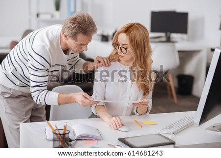 Aged business manager touching colleagues shoulder in the office